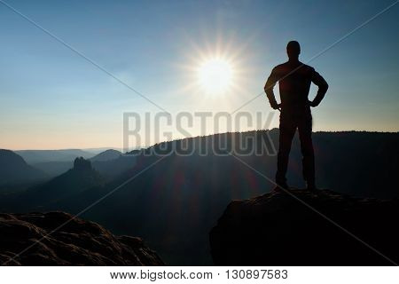 A Man Has His Hands On  Hips. Sportsman  Silhouette In Nature At Daybreak.