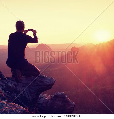Young Man In Black Sportswear Is Sitting On Sharp Cliff And Taking Photos By Smart Phone