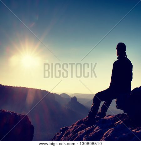 Tall Short Hair Hiker In Shirt Sit On A Rock And Enjoy Foggy Scenery In Mountains