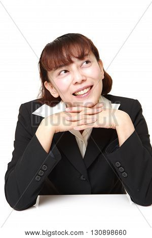 portrait of Asian businesswoman dreaming at her future on white background