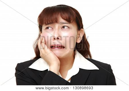 portrait of Asian businesswoman suffers from toothache on white background