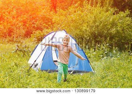 Cute Small Boy Runs Happy Near A Tent On Nature Background .