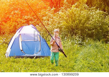 Cute Small Boy Stand Near A Tent With A Fishing Rod In His Hands.