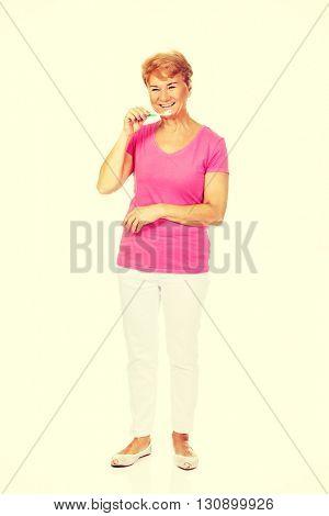 Smiling senior woman brushing teeth