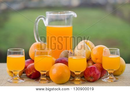 glasses of orange juice and lots of fruits on wooden table outdoor