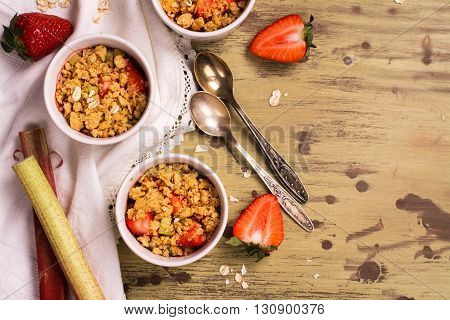 Crumble with strawberry, oat and rhubarb over wooden table. Top view