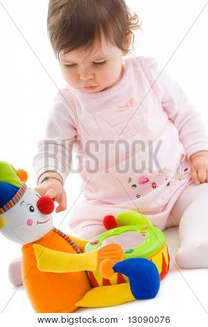 Happy baby girl sitting on floor playing with toy smiling, cotout on white background.