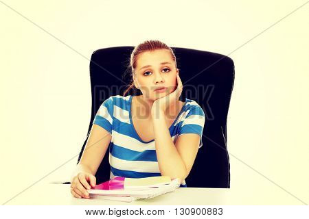 Tired teenage woman sitting behind the desk
