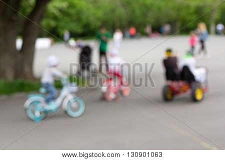 Defocused and blurred kid activity image: kids riding their bikes in the park