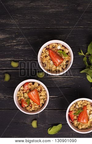 Crumble with strawberry, oatmeal and rhubarb over vintage black wooden table. Top view