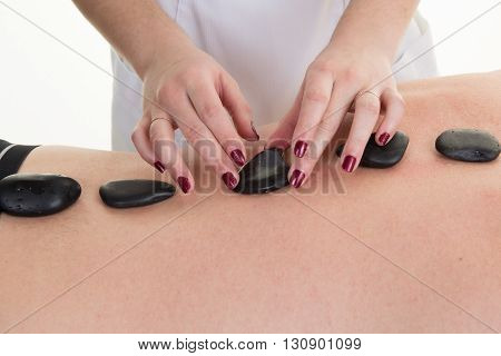 Man Laying On Massage Bed With Hot Stones On Body