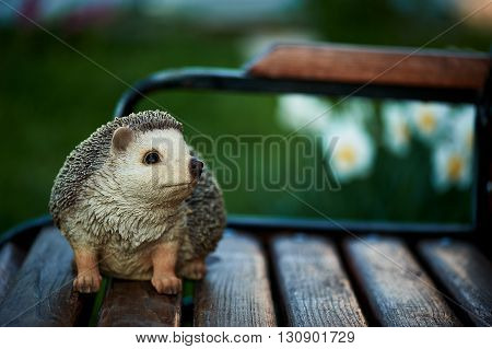 naturalistic statuette of a hedgehog standing on garden bench
