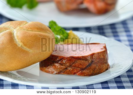 Portion of oven fresh Bavarian meat loaf with a crispy roll and mustard