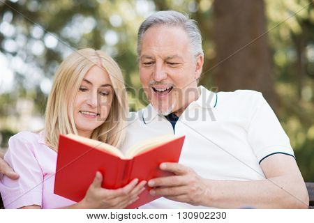 Portrait of an happy mature couple reading a book together