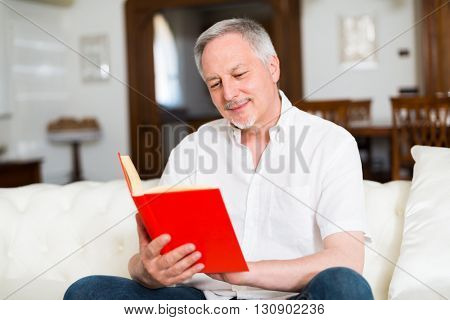 Portrait of an happy mature man reading a book