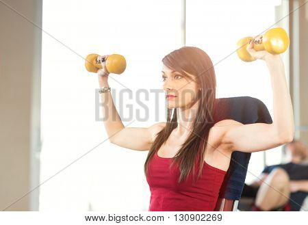 Young woman training in a gym. Controlled flare