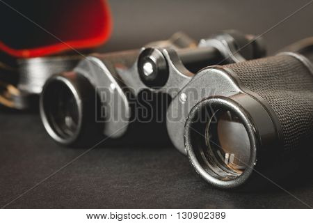 Old binoculars with strap and red case on black background