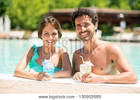 Smiling couple holding a cocktail in the pool