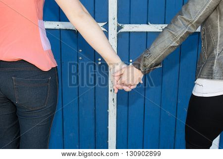 Close Up Of Happy Lesbian Couple Holding Hands Over Blue Background