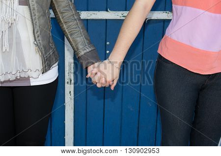Sweet Lesbian Couple Holding Hands Over Blue