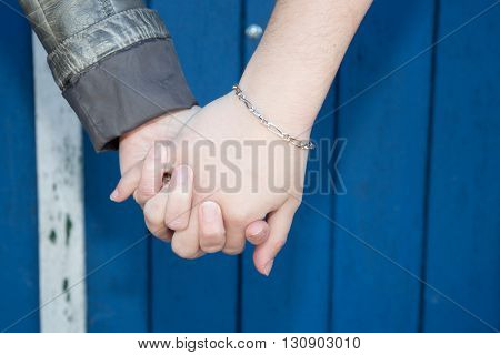 Hands Of Female Couple Holding Hands Over Blue