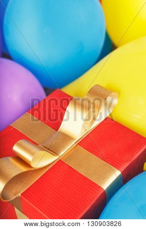 Red gift box with gold ribbon and bow in balloons with place for your text