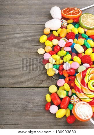 Variety of candy and gum on wooden table top view