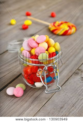 Glass jar of colorful candies on a wooden table closeup