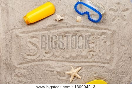 inscription on the sand - summer with a mask for swimming suntan lotion and seashells with starfish