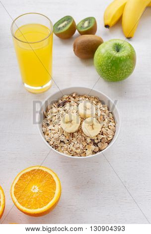 Granola with fruit and orange juice on a light wooden surface. Healthy and tasty food