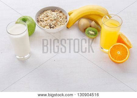 Granola bananas glass of orange juice kiwi and a glass of milk on a light wooden surface with free space for your text. Food for a healthy and tasty food