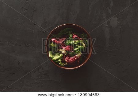 Fresh salad on a dark background top view. Helpful and simple food