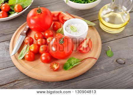 set of tomato on the wooden table with green salad leaves. Ingredients for the preparation of wholesome food