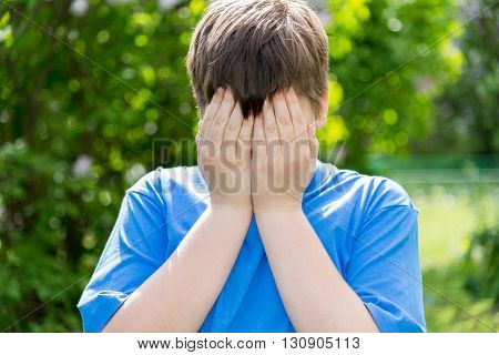 teen problems - a boy covered his face with his hands outside