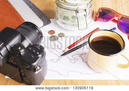 Traveling cocept with map drawing dollar banknotes in jar photo camera coffee in iron mug coins pencils and sunglasse