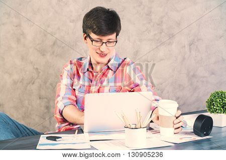 Frontview of caucasian man using laptop on wooden office desk