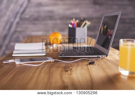 Side view of designer desktop with laptop smartphone office tools and orange. Angled laptop on table in home interior. Freelance desktop with open laptop computer