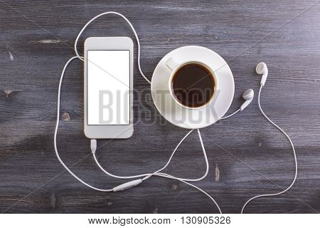 Topview of dark wooden desktop with coffee cup and saucer blank white mobile phone and headphones. Mock up