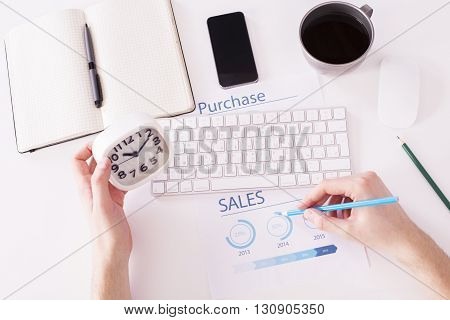 Top view of white office desktop with male hands holding clock and drawing pie-chart on business report paper