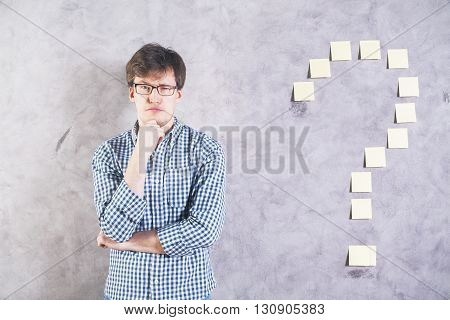 Thoughtful man raising one of his eyeborws standing against concrete wall with sticker question mark