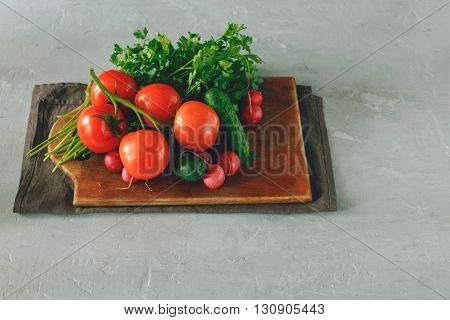 Set of fresh vegetables on the light surface on a wooden kitchen board. Branch tomatoes bunch of parsley radishes and cucumbers. Helpful and diet food