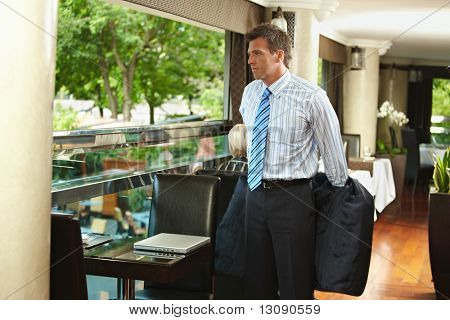 Businessman taking off his suit and sitting down to coffee table in elegant cafe.