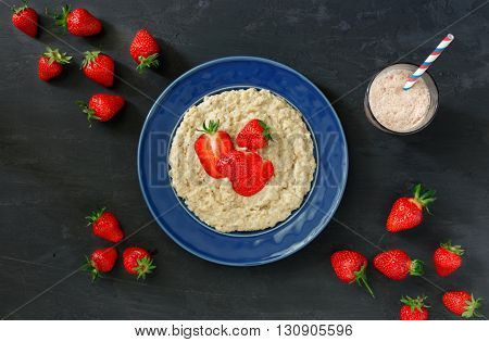Oatmeal porridge with strawberries in vintage blue plate on a dark surface with ice cream milkshake top view. Healthy breakfast