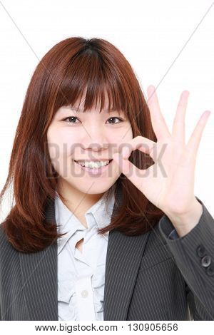 portrait of businesswoman showing perfect sign on white background