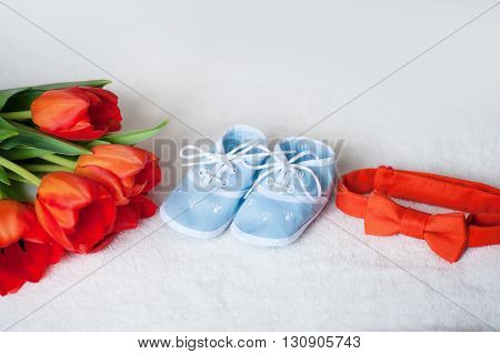 red tulips tie and children blue boots on  white background.
