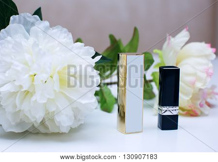 Women's cosmetics. perfume and lipsticks with flowers