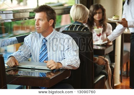 Businessman sitting at coffe table in cafe, waiter serving sweets to young women in the background.