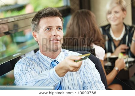 Closeup portrait of businessman sitting at coffe table in cafe, paying with credit card, smiling.