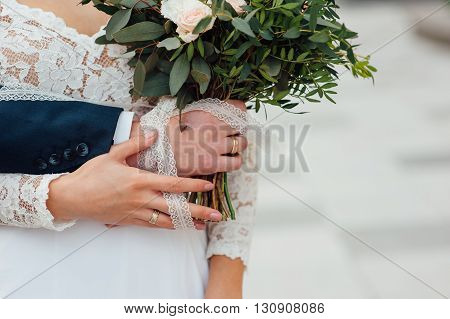 Bride And Groom Together Holding Wedding Bouquet