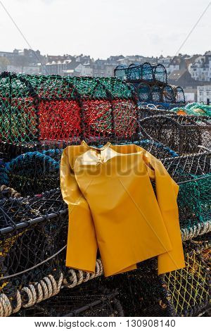 SCARBOROUGH ENGLAND - MAY 5: Trawlerman's protective oilskin smock and lobster pots in the harbour. In Scarborough England. On 5th May 2016.